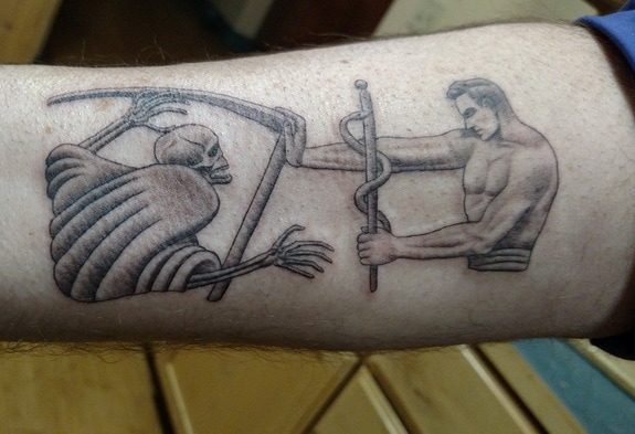 Tattoo of a medic fighting off death: the man holding the classic skeletal image of death with his scythe, and the man holding the Rod of Asclepius